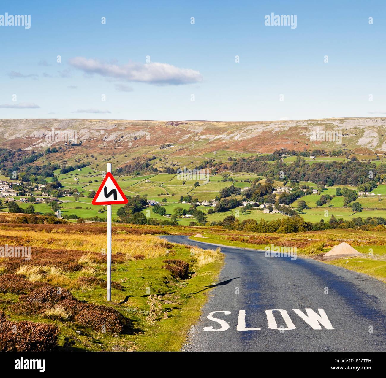 Cartello stradale di avvertimento di curve pericolose davanti e lenta dipinta sulla superficie della strada, Yorkshire Dales National Park, England, Regno Unito Immagini Stock