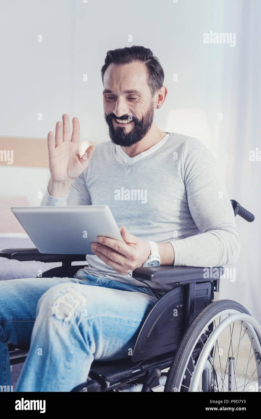 Uomo positivo con disabilità sorridere mentre avente una chiamata video Immagini Stock