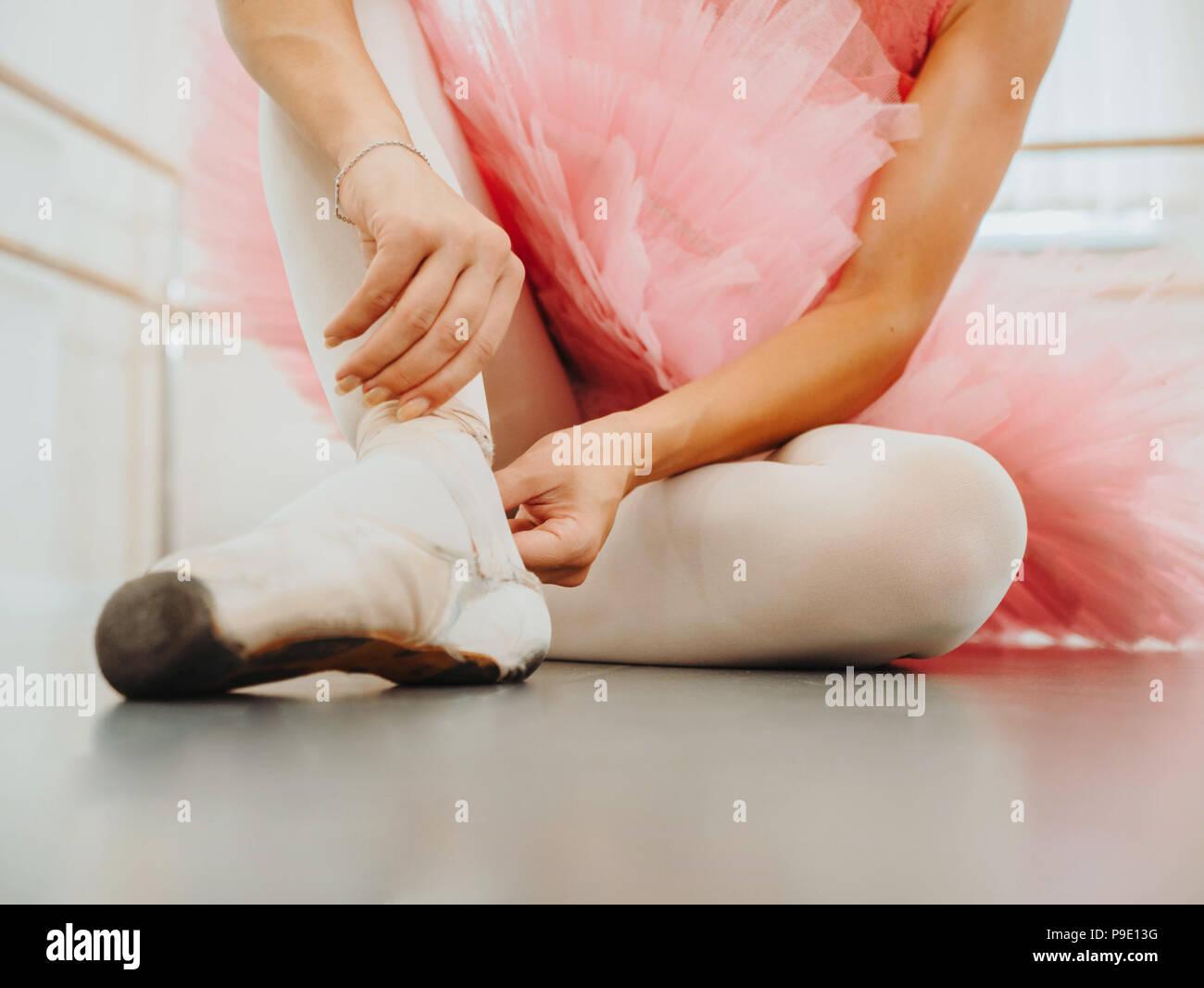 Giovane ballerina in tutù rosa avvolge il costume di nastri di seta bianca di soft top scarpe da ballo pointe e li collega. La donna la preparazione per la danza lezioni di training in palestra. Immagini Stock