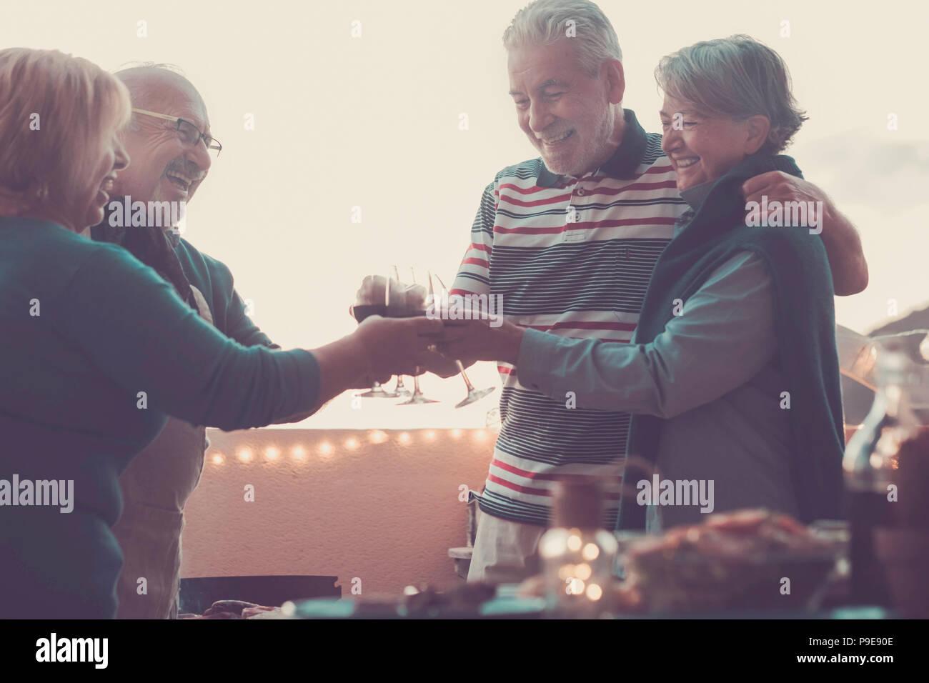 Senior persone adulte gruppo in attività del tempo libero facendo barbecue barbecue sulla terrazza sul tetto di casa con vista montagna. pasto e vino per due uomini e due Immagini Stock