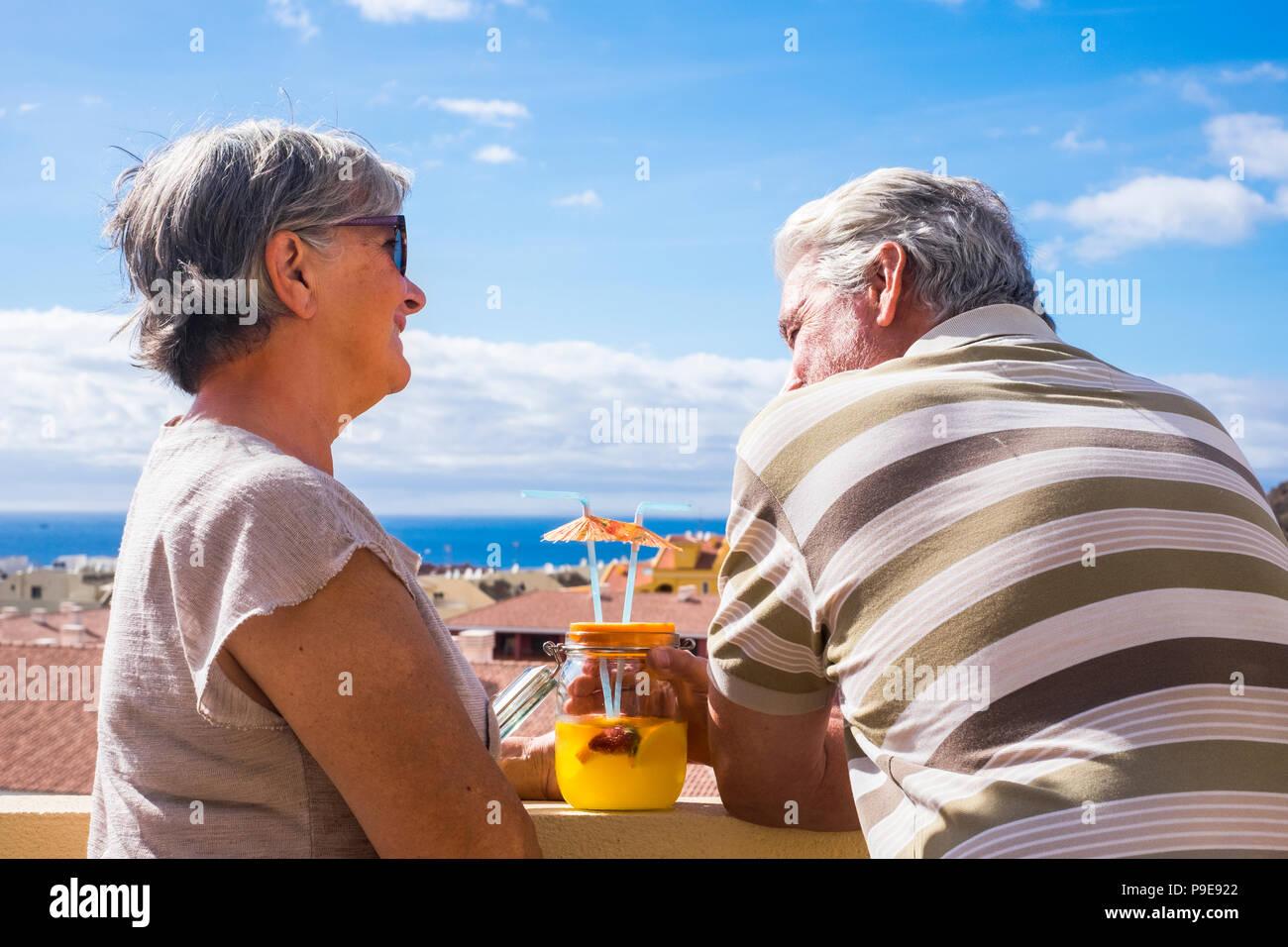 Bella coppia di pensionati soggiorno adulti insieme sul roofto pterrace bere e mangiare un po' di cibo e bevanda. sorriso persone all'aperto in grande lifesty Immagini Stock