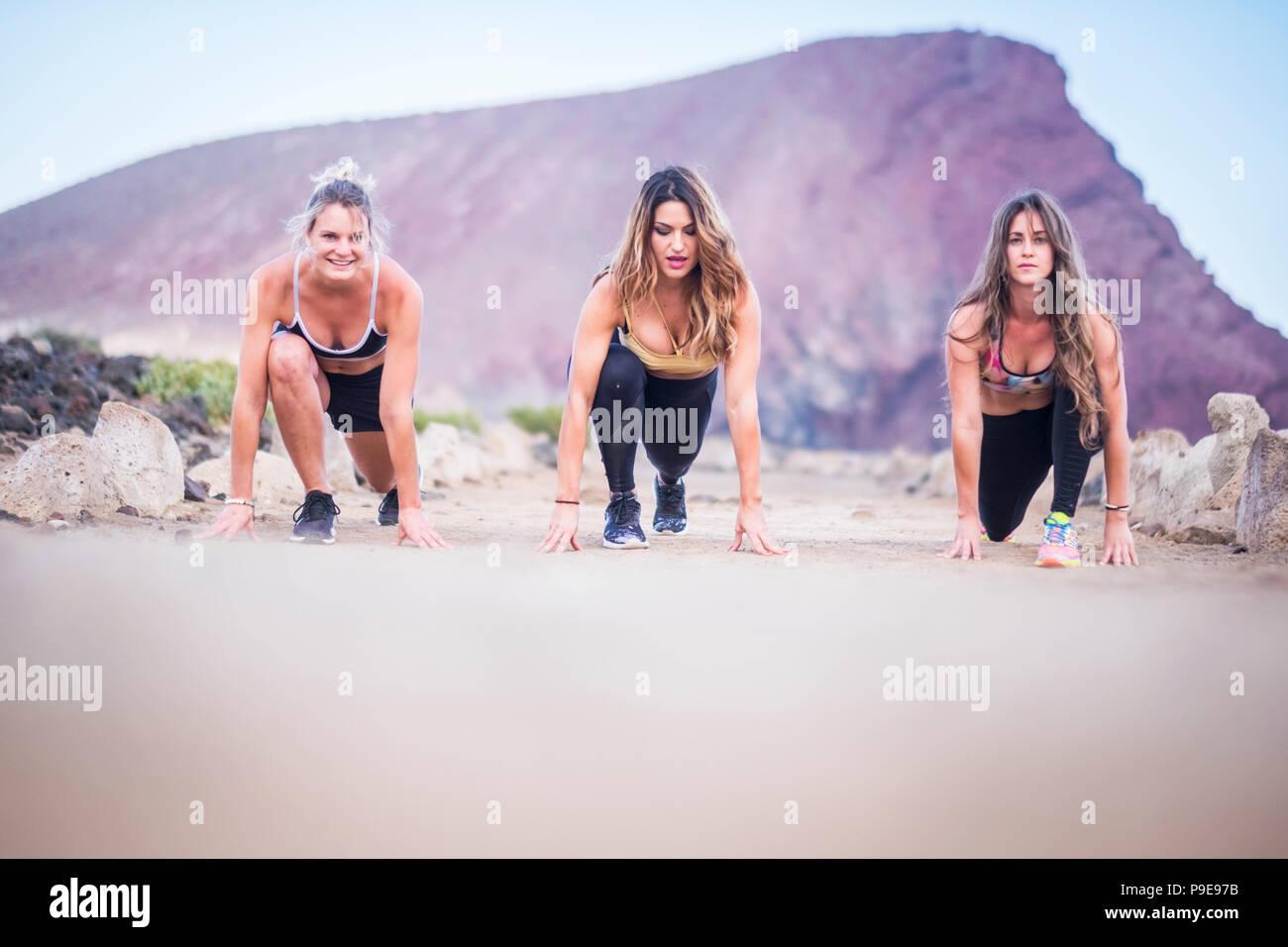 Tre belle ragazze runner giovani pronti per avviare e far funzionare per il duro allenamento fitness e attività all'aperto. Costruisci il tuo nuovo e forte corpo vicino alla spiaggia Immagini Stock