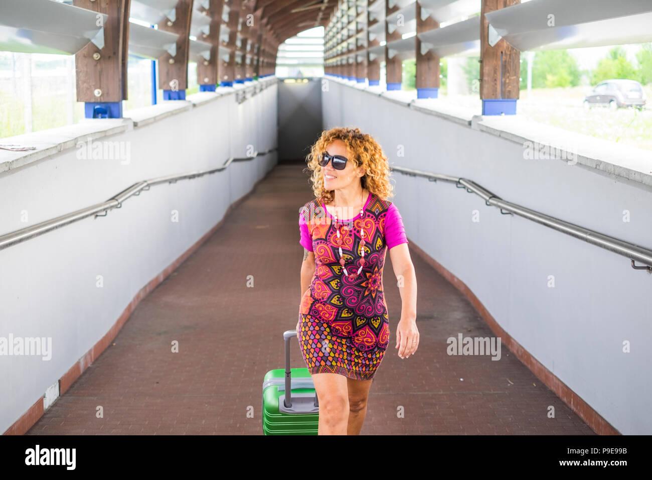 Bella donna viaggiatore a piedi al di fuori della stazione ferroviaria per arrivare a destinazione. wanderlust per viaggiatori indipendenti femmina caucasica sorridente e loo Immagini Stock