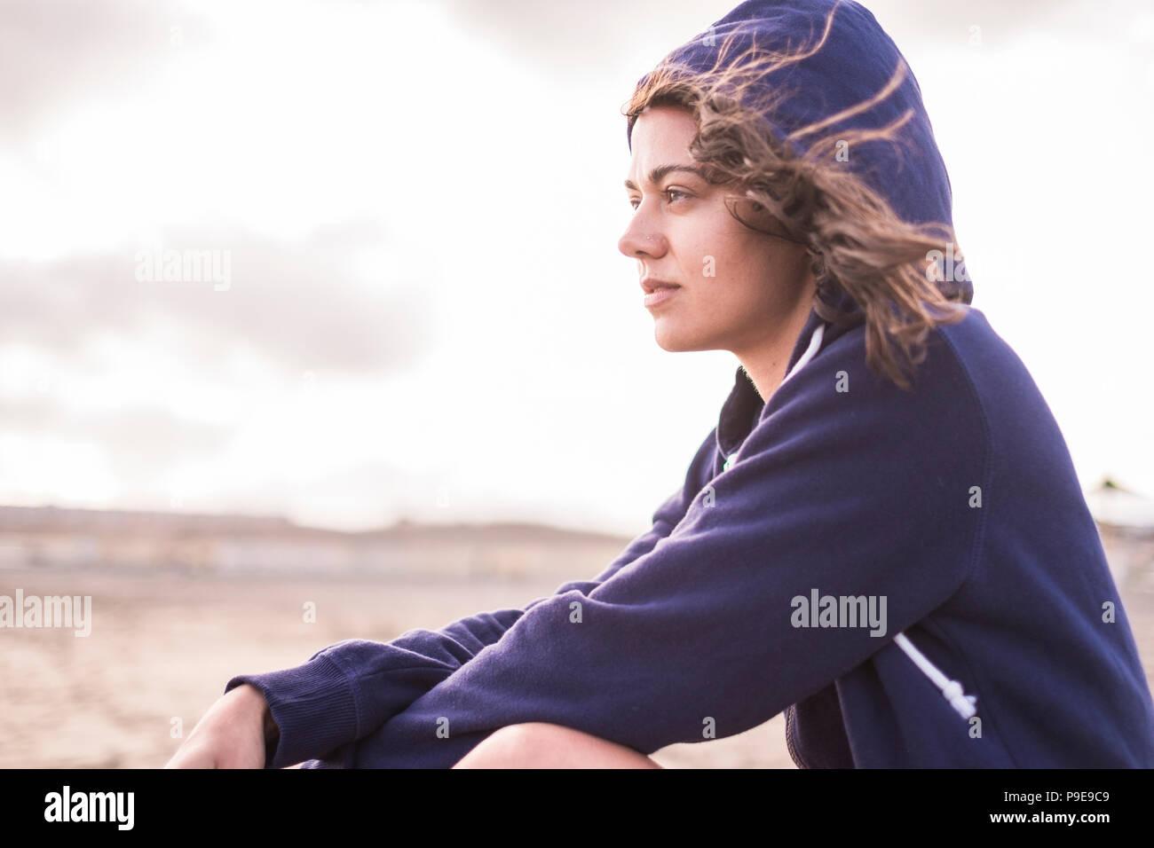 Bella ragazza seduta sulla spiaggia all'aperto in estate vacanze. perso nei suoi pensieri con indipendenza e libertà concetto. cielo luminoso con le nuvole in Immagini Stock