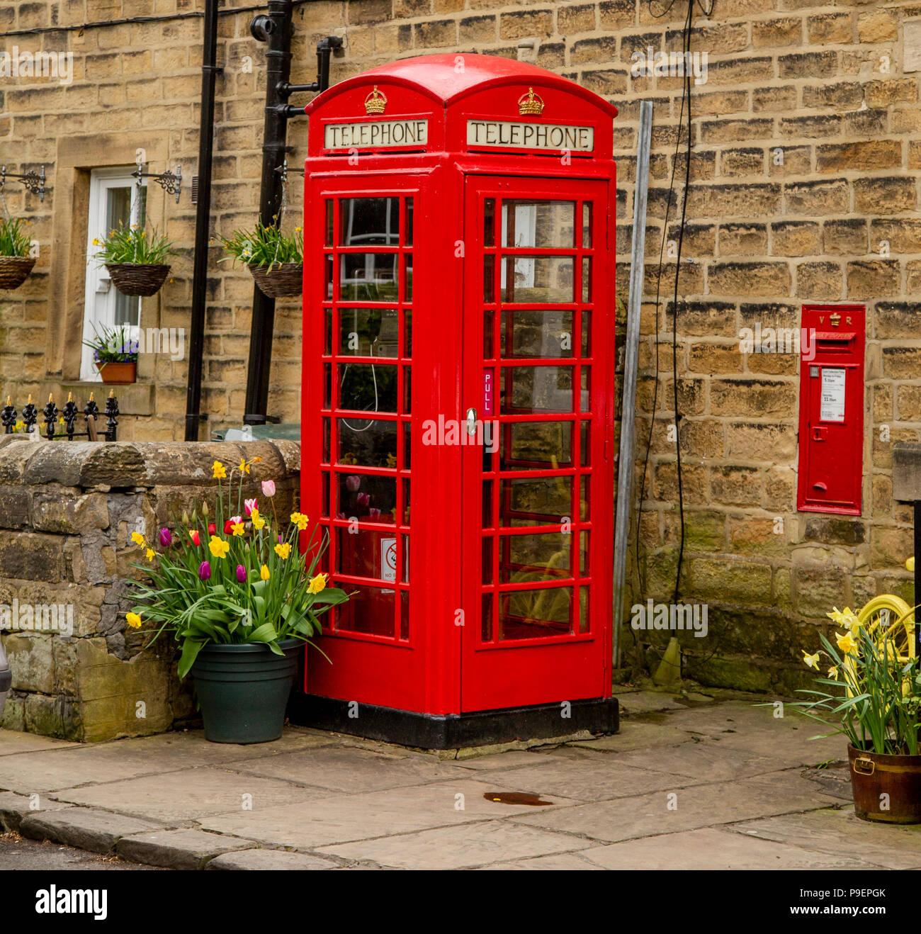 Un K6 telefono rosso scatola (UK) e la parete postbox in Esholt, West Yorkshire, Inghilterra. Foto Stock