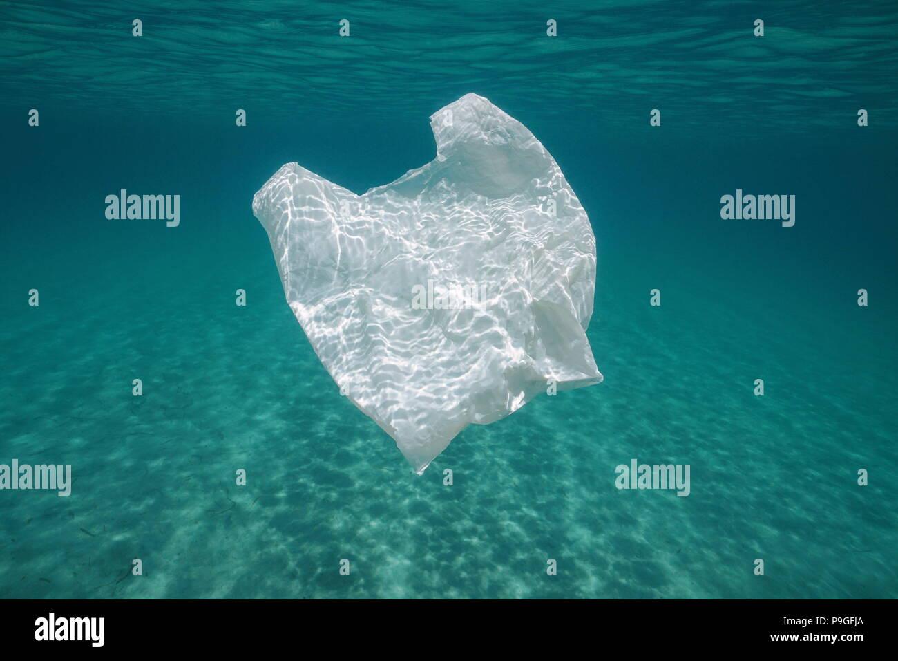 Inquinamento subacquea in una borsa di plastica in mare tra la superficie dell'acqua e un fondale sabbioso, Mediterraneo Almeria, Andalusia, Spagna Immagini Stock