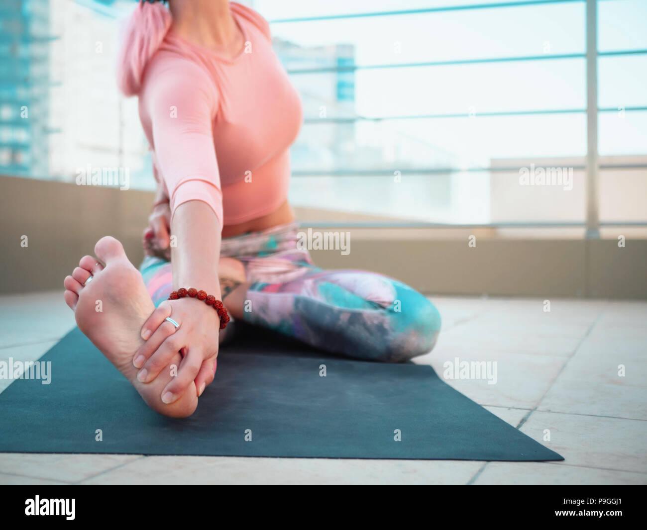 Giovane donna slim con rosa capelli tinti facendo yoga pratica sulla terrazza della città moderna. Ragazza per tenersi in forma e corpo sano relax sulla terrazza sul tetto durante la pratica, rappresentano Foto Stock