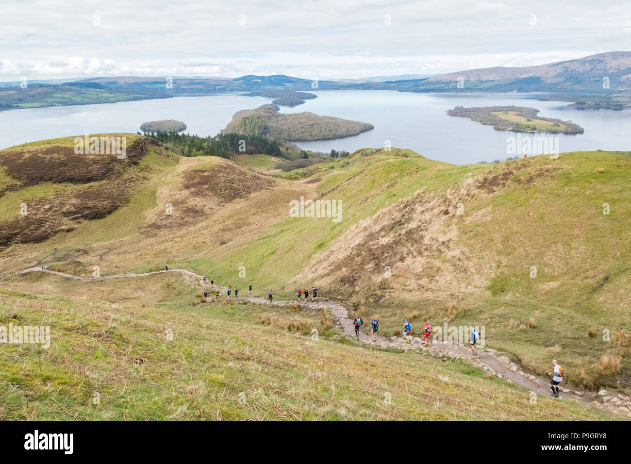 Concorrenti conico decrescente collina che si affaccia sul Loch Lomond Scozia, Regno Unito durante le Highland Fling Festival ultra maratona trail - Aprile 2018 Immagini Stock