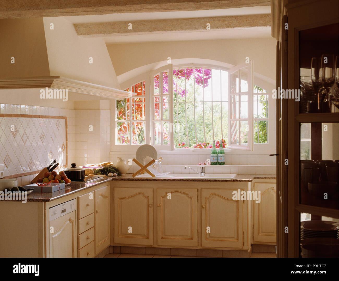 Crema paese francese cucina con lavello sotto la finestra aperta per ...