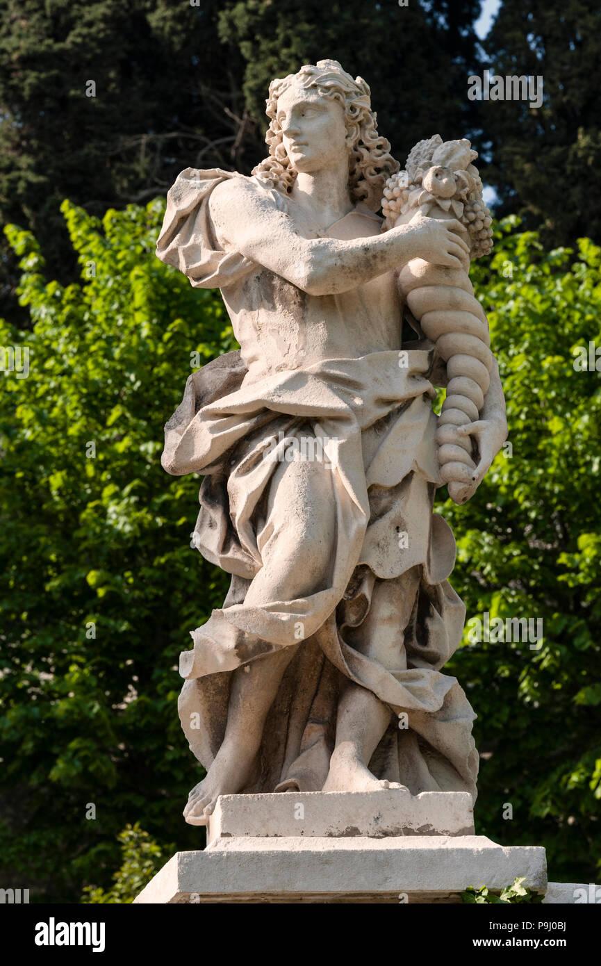 Veneto, Italia. Statua di un dio classico (probabilmente Plutus, figlio di Demetra) portante una cornucopia, simbolo di ricchezza, la ricchezza e la prosperità Immagini Stock