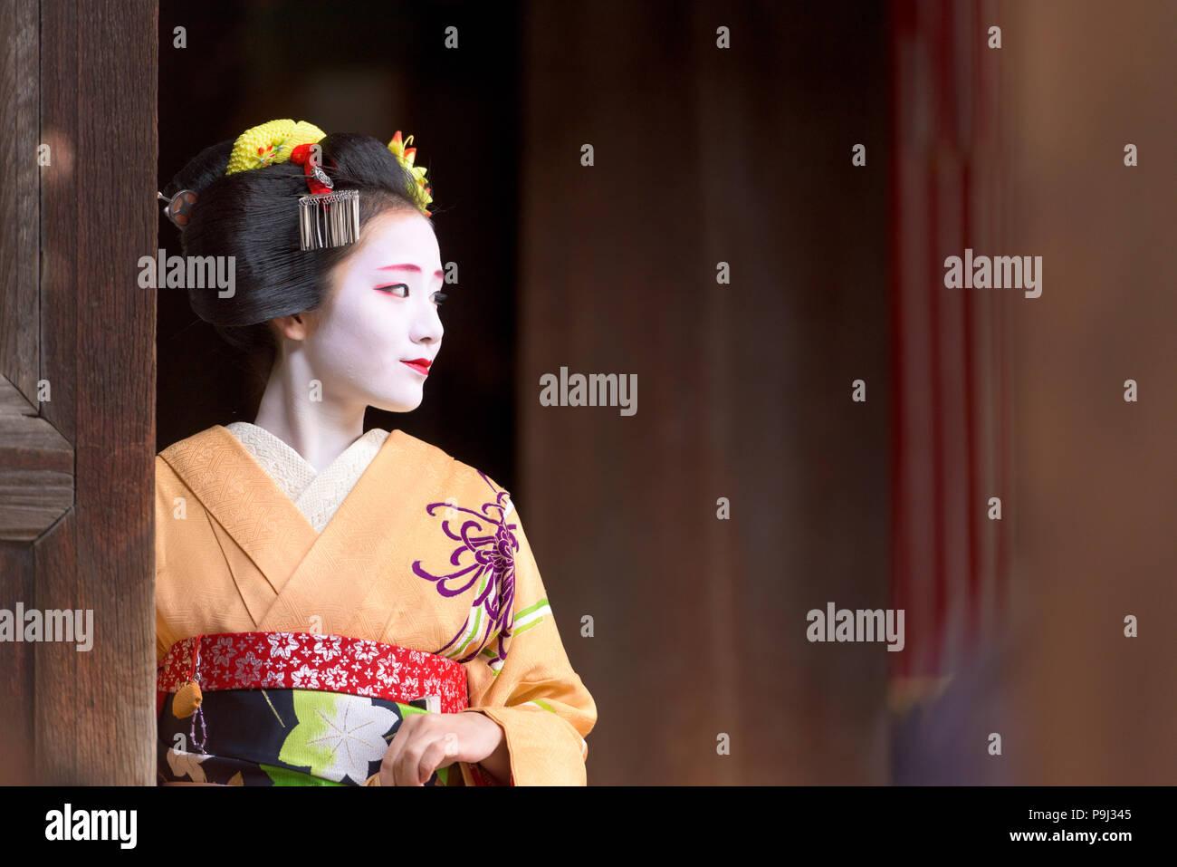 KYOTO, Giappone - 28 novembre 2015: una donna nel tradizionale abito Maiko si affaccia da un tempio porta. Immagini Stock