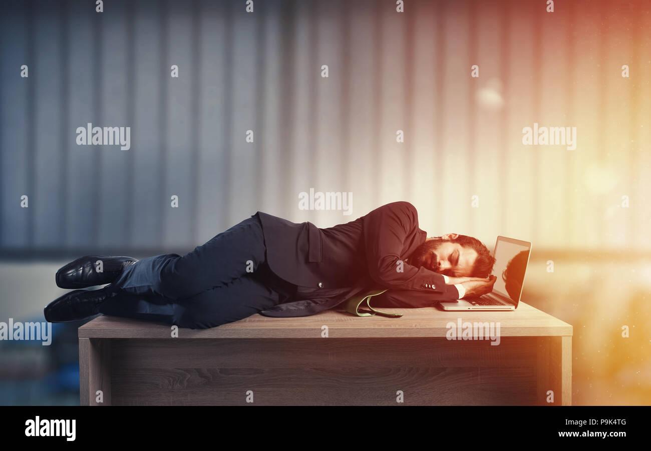 Imprenditore dormendo su una scrivania a causa di sovraccarico di lavoro Immagini Stock