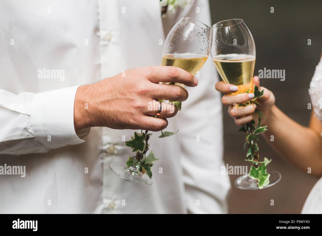 L uomo e la donna mani due bicchieri di champagne decorato con fiori per la cerimonia di nozze Immagini Stock