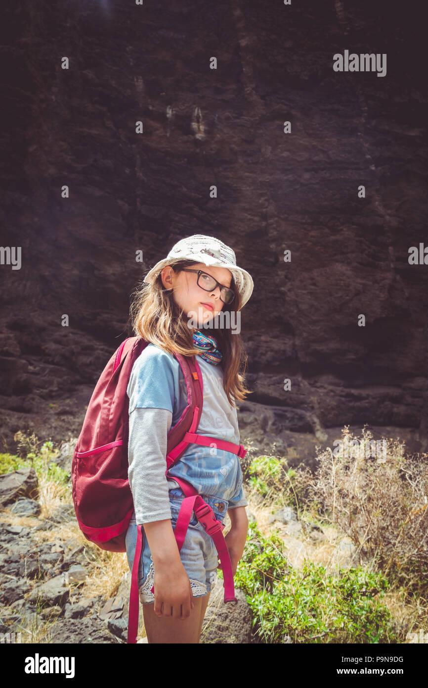 Una ragazza caucasica bambino pause durante una passeggiata in un giorno  caldo contro una montagna rocciosa a2f999c3213a