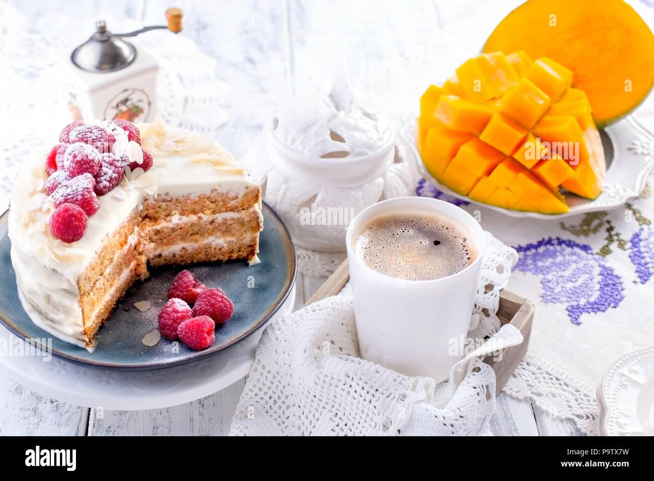 Tagliare la torta con crema bianca per la prima colazione. Un frutto di mango. Sfondo bianco, tovaglia con pizzo, una tazza di fragranti caffè nero e spazio libero per il testo o per la pubblicità. Immagini Stock