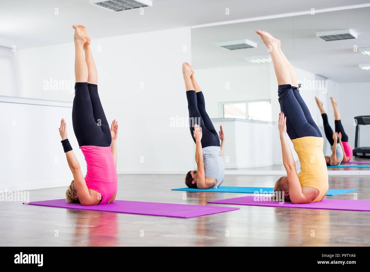 Le tre ragazze la pratica dello yoga, Sarvangasana / Spalla stand pongono Immagini Stock