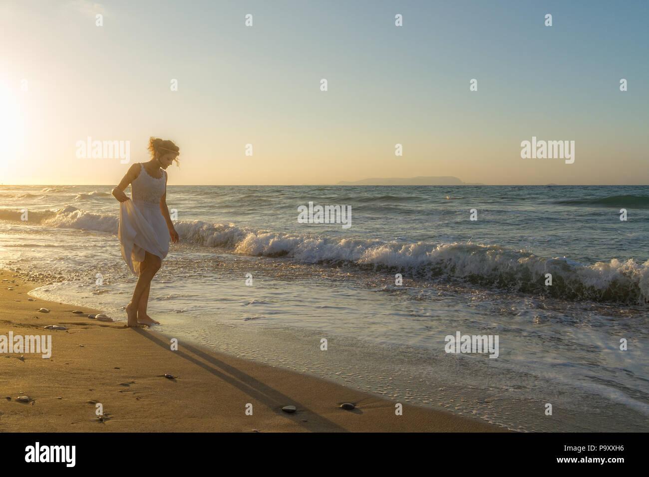 Donna in abito bianco, scalzi, sentirsi felice, vivo e libero in natura meditando a Sandy misty respirazione spiaggia fresca e pulita aria dell'oceano al tramonto. Vacanze estive il concetto di stile di vita Immagini Stock