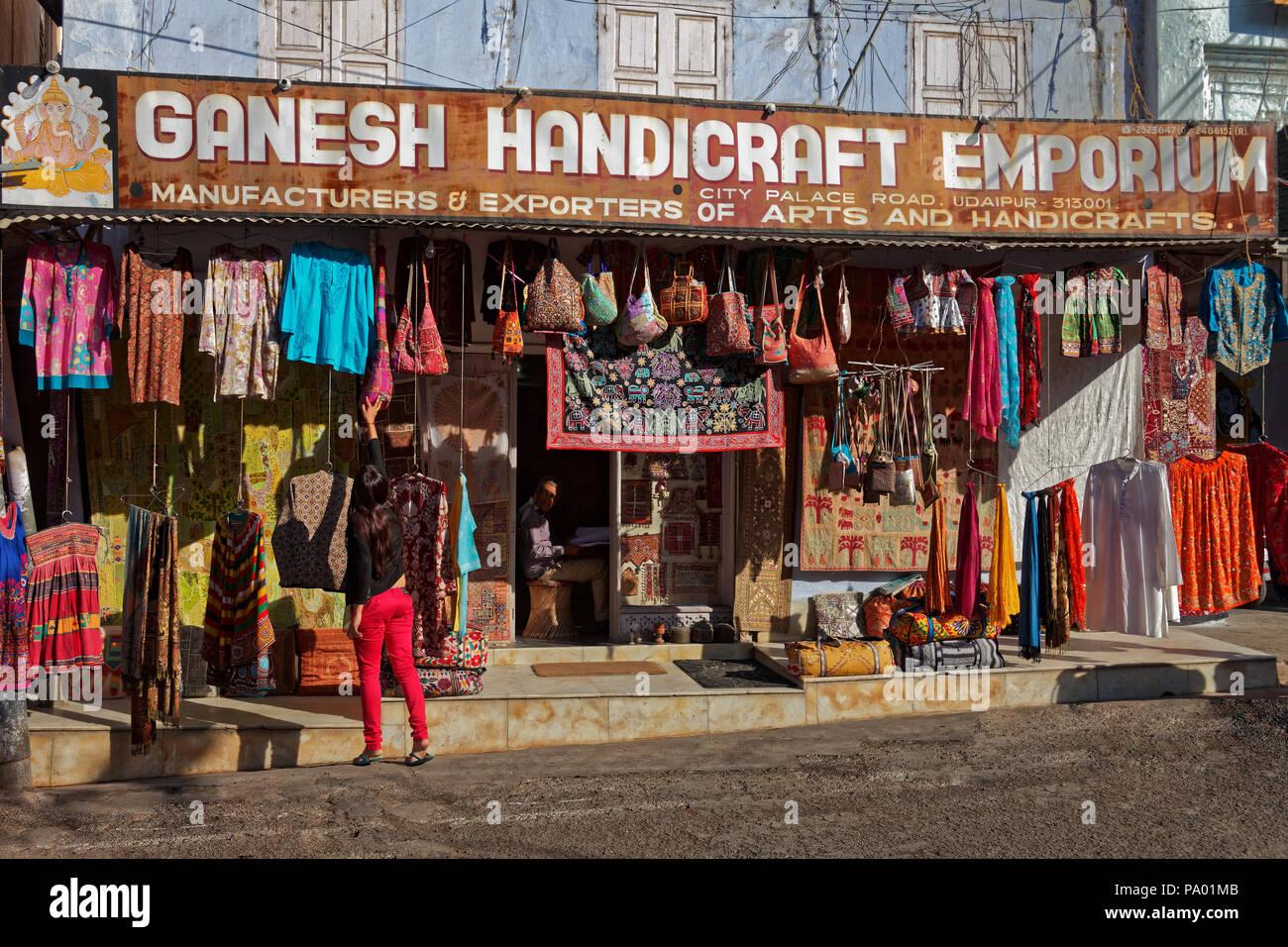 Ragazza acquistare un sacchetto da un negozio di artigianato, Udaipur, Rajasthan, India Immagini Stock