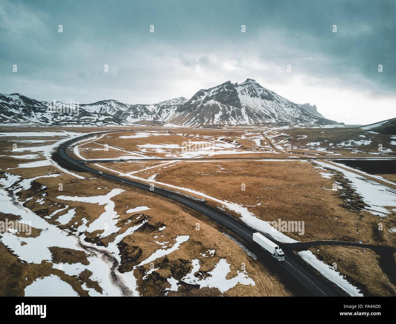 L' Islanda , febbraio 2018: un camion è passante lungo una strada con vista aerea del paesaggio con la neve e le nuvole street e il giallo e il verde del prato. Immagini Stock