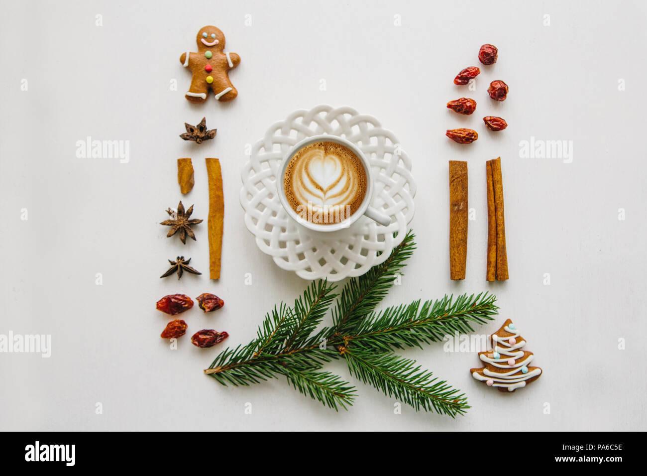 Freschi e deliziosi caffè cappuccino in una tazza con un motivo floreale. Vicino a vari elementi di Natale o il tema di inverno Immagini Stock