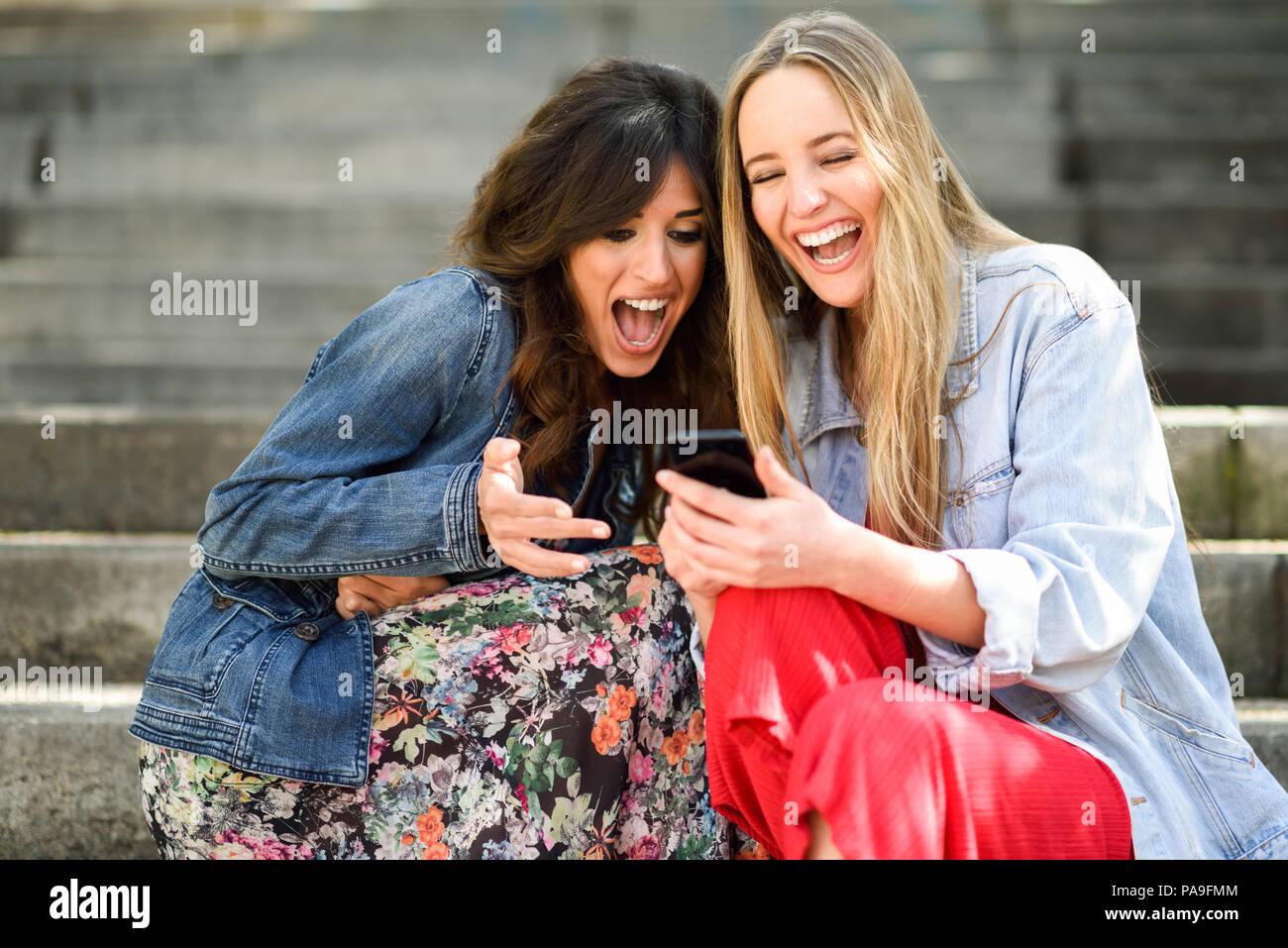 Due giovani donne guardando alcune divertenti cosa sulla loro smart phone all'aperto, seduti su fasi urbane. Gli amici le ragazze a ridere. Immagini Stock