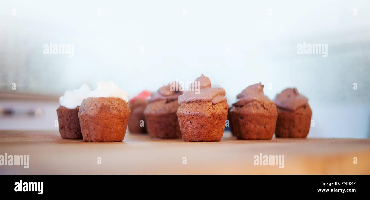 Muffin al cioccolato sulla scrivania. Tortine con creme diverse. Copia spazio sulla parte superiore Immagini Stock