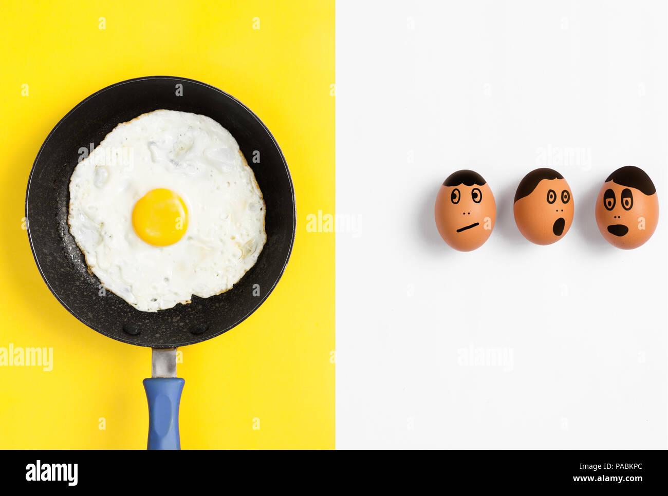 Uovo fritto in padella con facce disegnato su uova crude guardando preoccupato, piatto laici immagine alimentare Immagini Stock