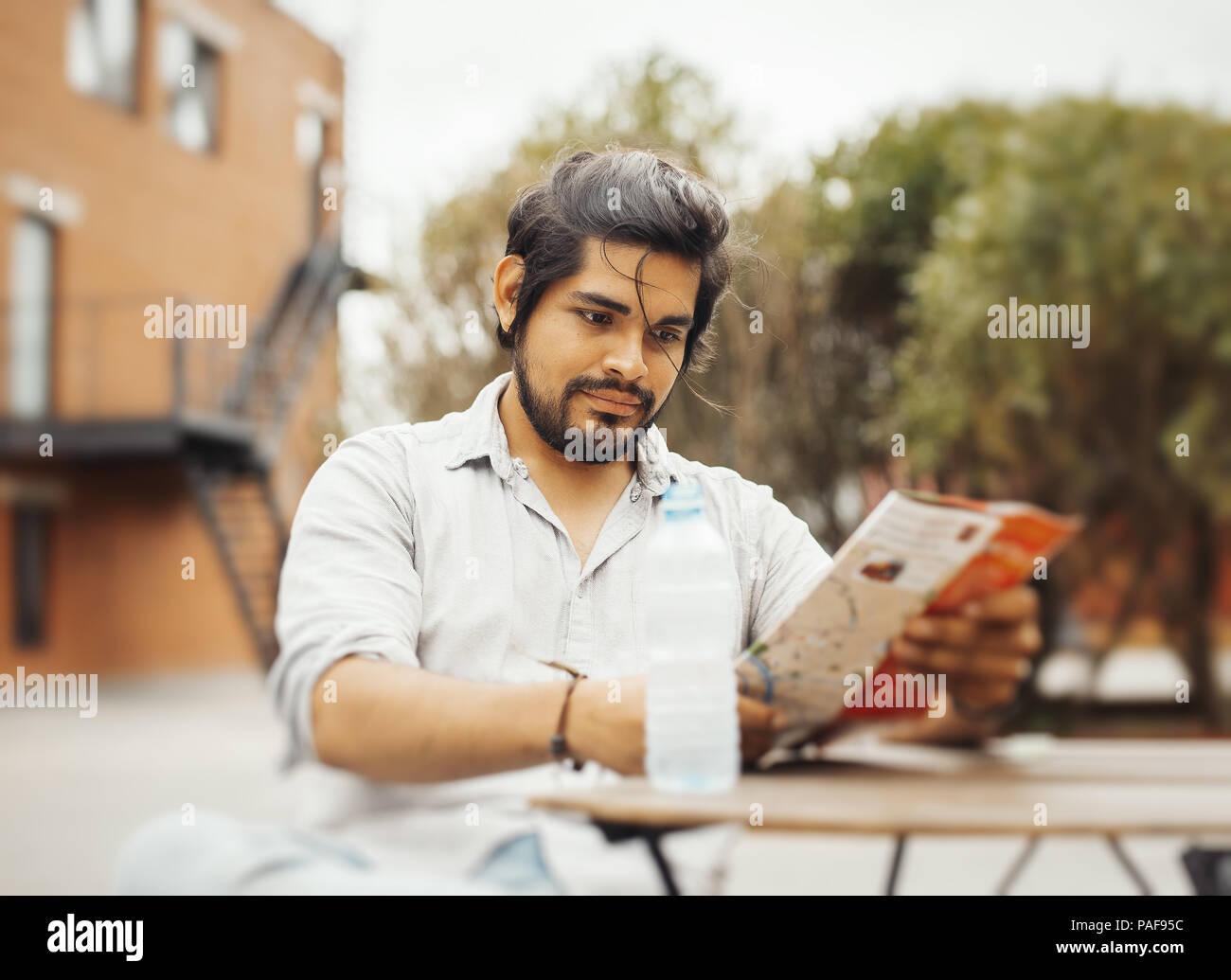 Attraente latino uomo seduto al street cafe e guardando la mappa. Immagini Stock