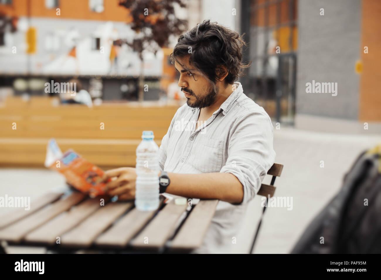 Attraente pensieroso uomo seduto al street cafe e guardando la mappa. Vista laterale Immagini Stock