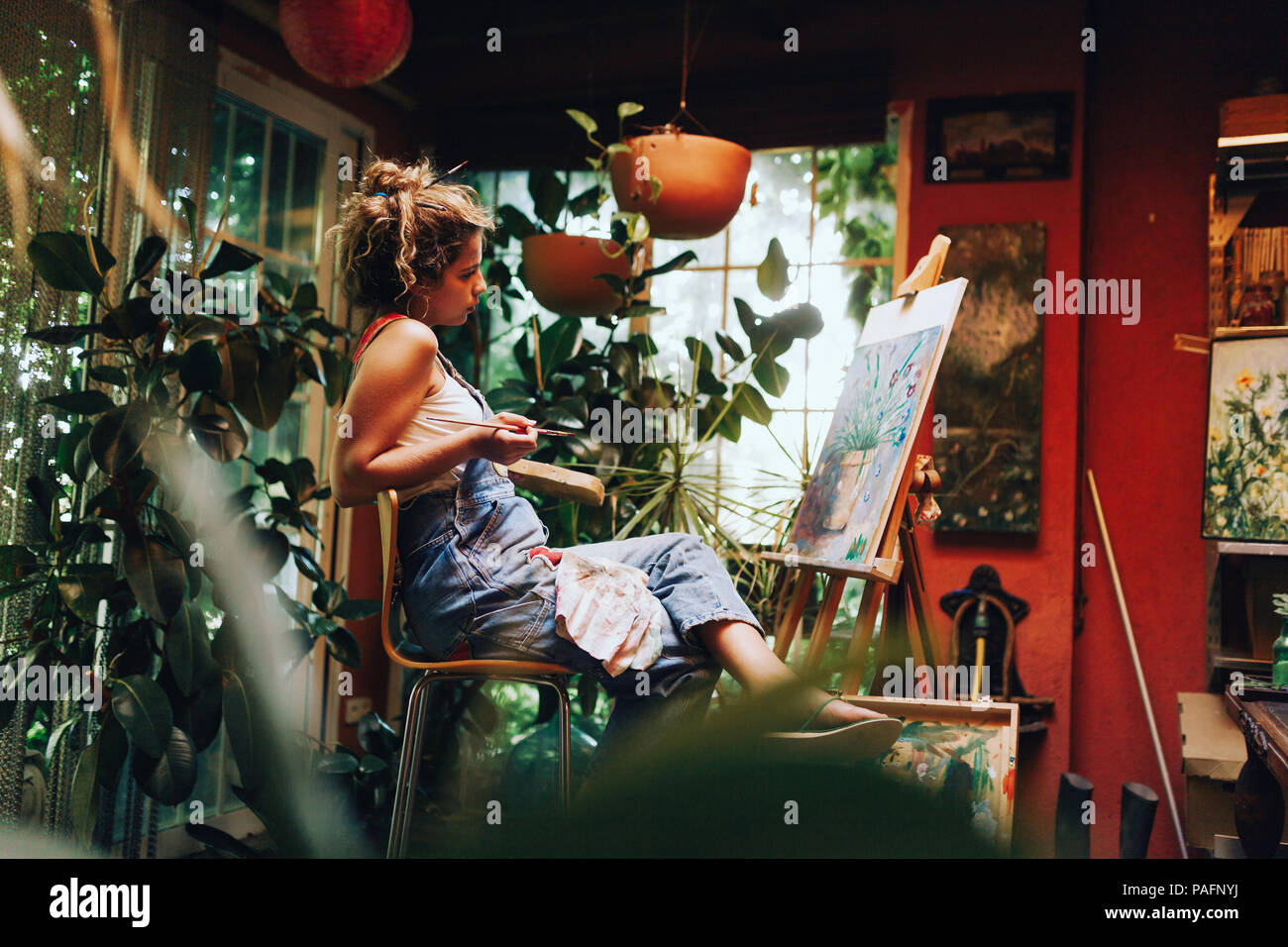 Piscina colpo di professional artista femminile dipinto su tela in studio con piante. Immagini Stock
