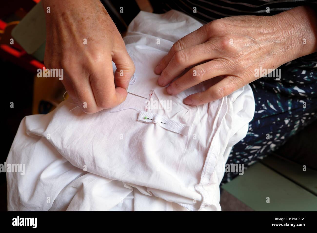 Close-up di una donna anziana con le mani in mano la riparazione di rammendo un foglio di cucitura bianco con nastro di cotone Wales UK KATHY DEWITT Immagini Stock
