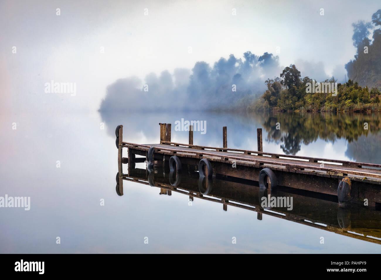 Pontile Lago Mapourika, nella costa occidentale della Nuova Zelanda, su una mattinata nebbiosa. Immagini Stock