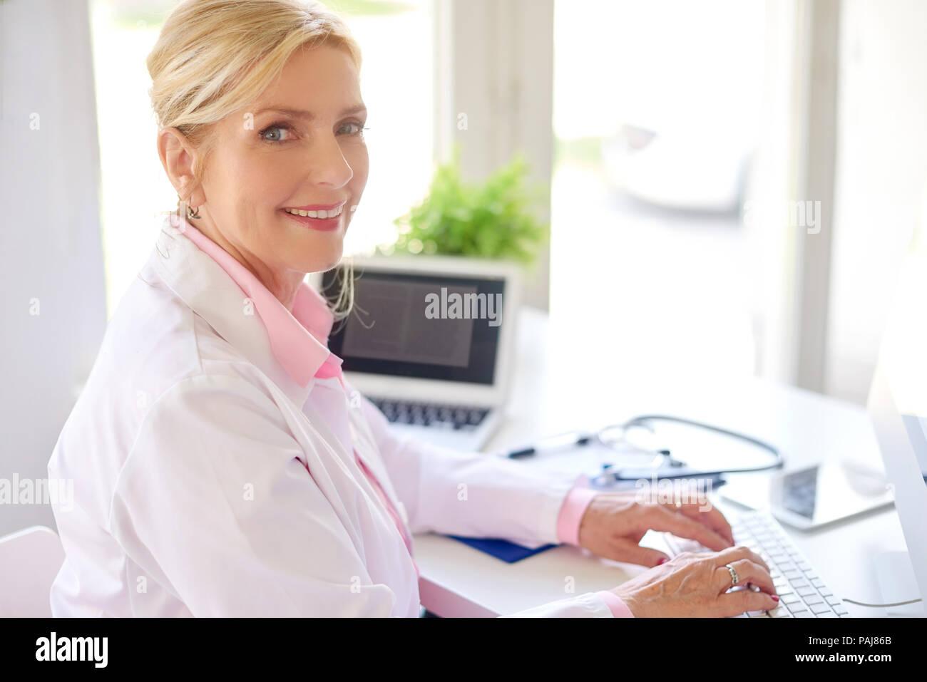 Sorridente senior femminile medico di ricerca utilizzando il computer portatile e mentre si lavora alla scrivania. Foto Stock