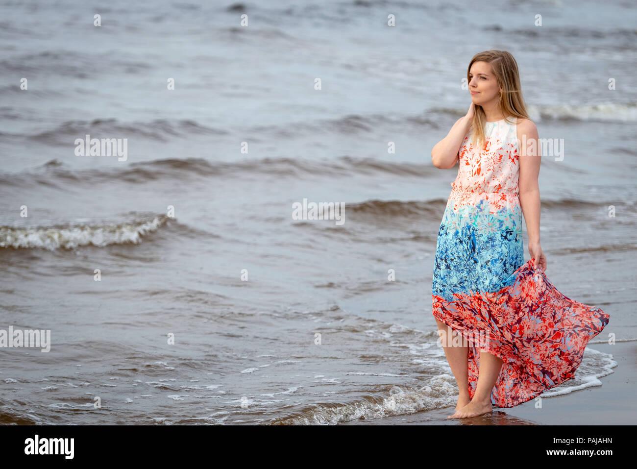 watch a5a55 0e35a Una giovane donna che cammina nel colorato lungo abito lungo ...