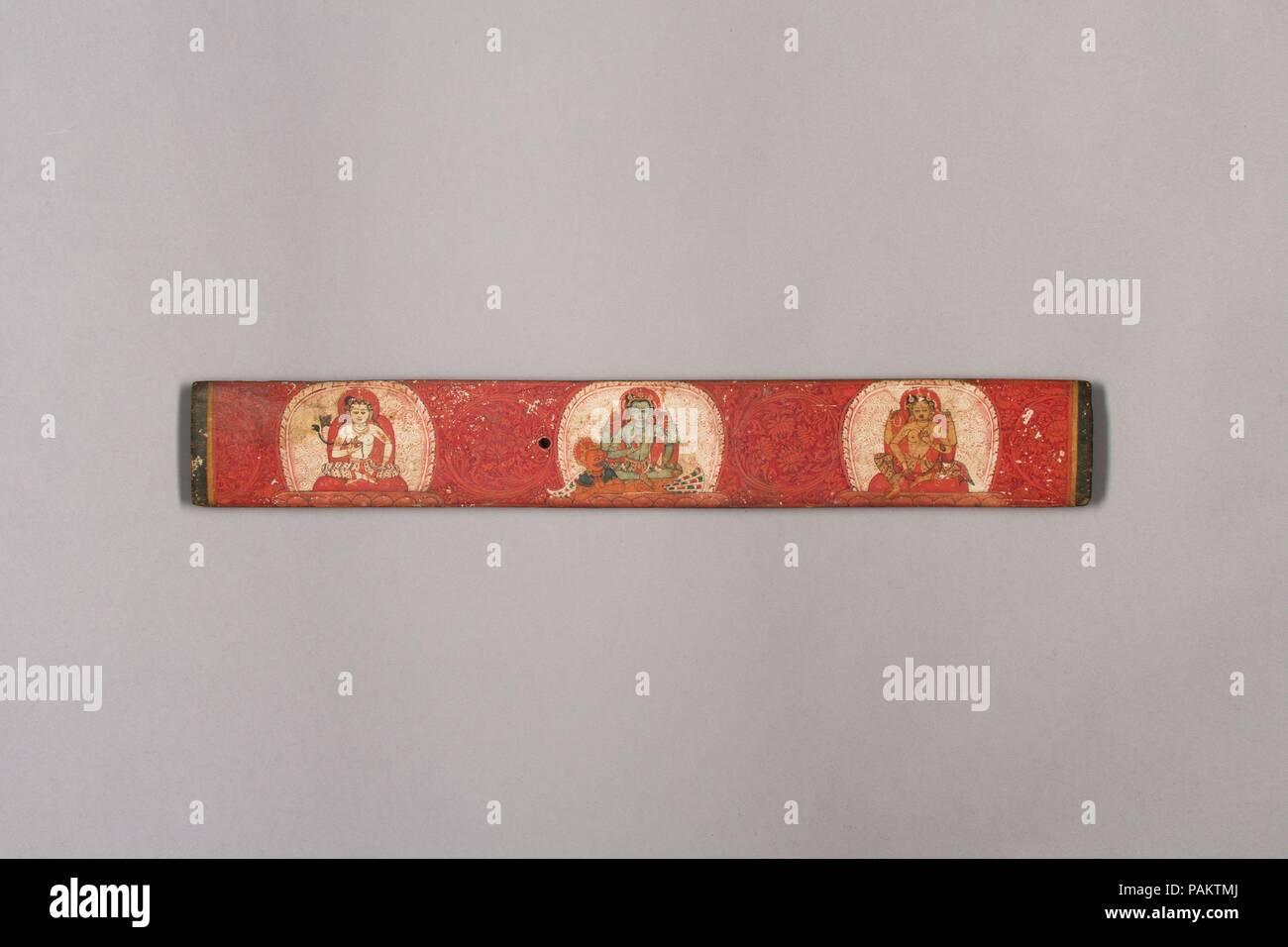 Manoscritto del coperchio con Vishnu affiancato da Lakshmi e Sarasvati. Cultura: Nepal (valle di Kathmandu). Dimensioni: complessivo: 1 7/8 x 13 1/16 in. (4,7 x 33,2 cm). Data: XIV secolo. Questo coperchio mostra permanente di quattro-armati Vishnu montato su Garuda, la sua metà uomo e metà uccello-veicolo. Vishnu è fiancheggiata sulla destra da sua moglie Lakshmi, la dea della ricchezza e prosperità e sulla sinistra di Sarasvati, la dea di apprendimento e di sapienza, che a volte appare come Vishnu la consorte. Tre di Vishnu a quattro mani tenere la sua solita attributi marziale, che egli utilizza quando egli aids devoti in necessità: il discus, clu Immagini Stock