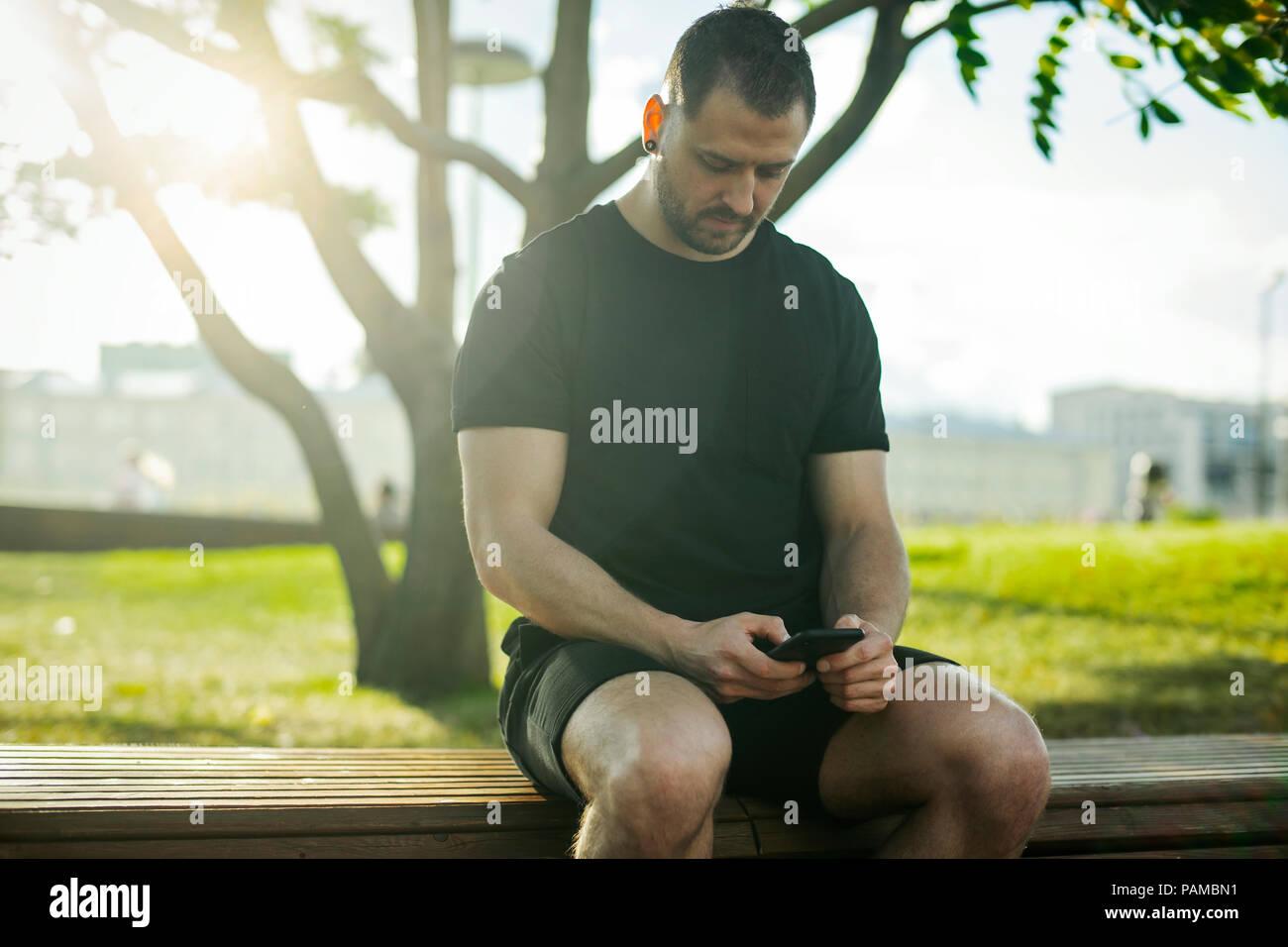 Chiusura del giovane uomo seduto al banco e la digitazione di un messaggio di testo sul telefono cellulare all'aperto nel parco. Vista frontale. Immagini Stock