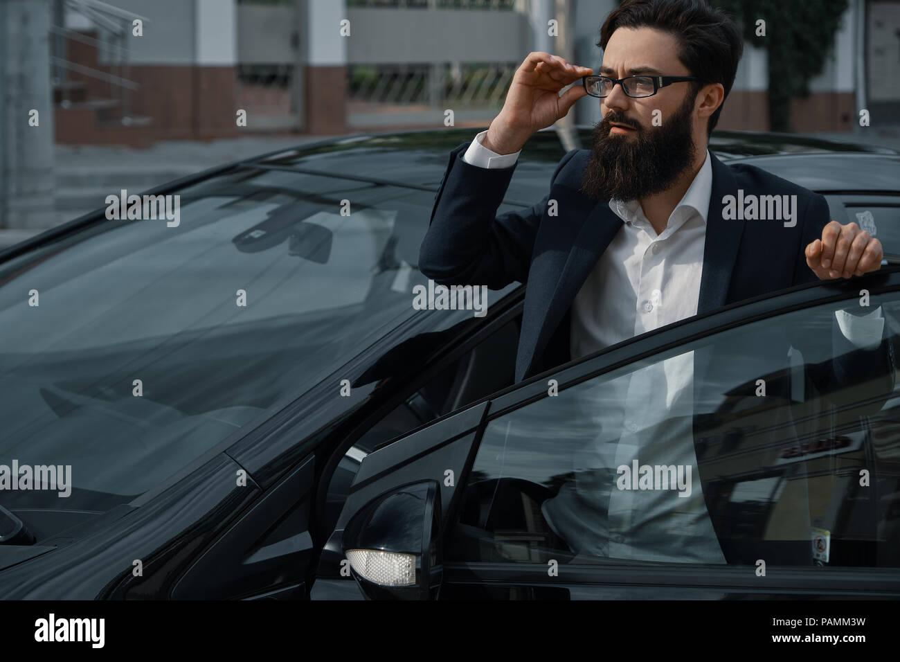 Fiducioso uomo in abbigliamento formale tenendo la mano aperta sulla porta auto wat Immagini Stock
