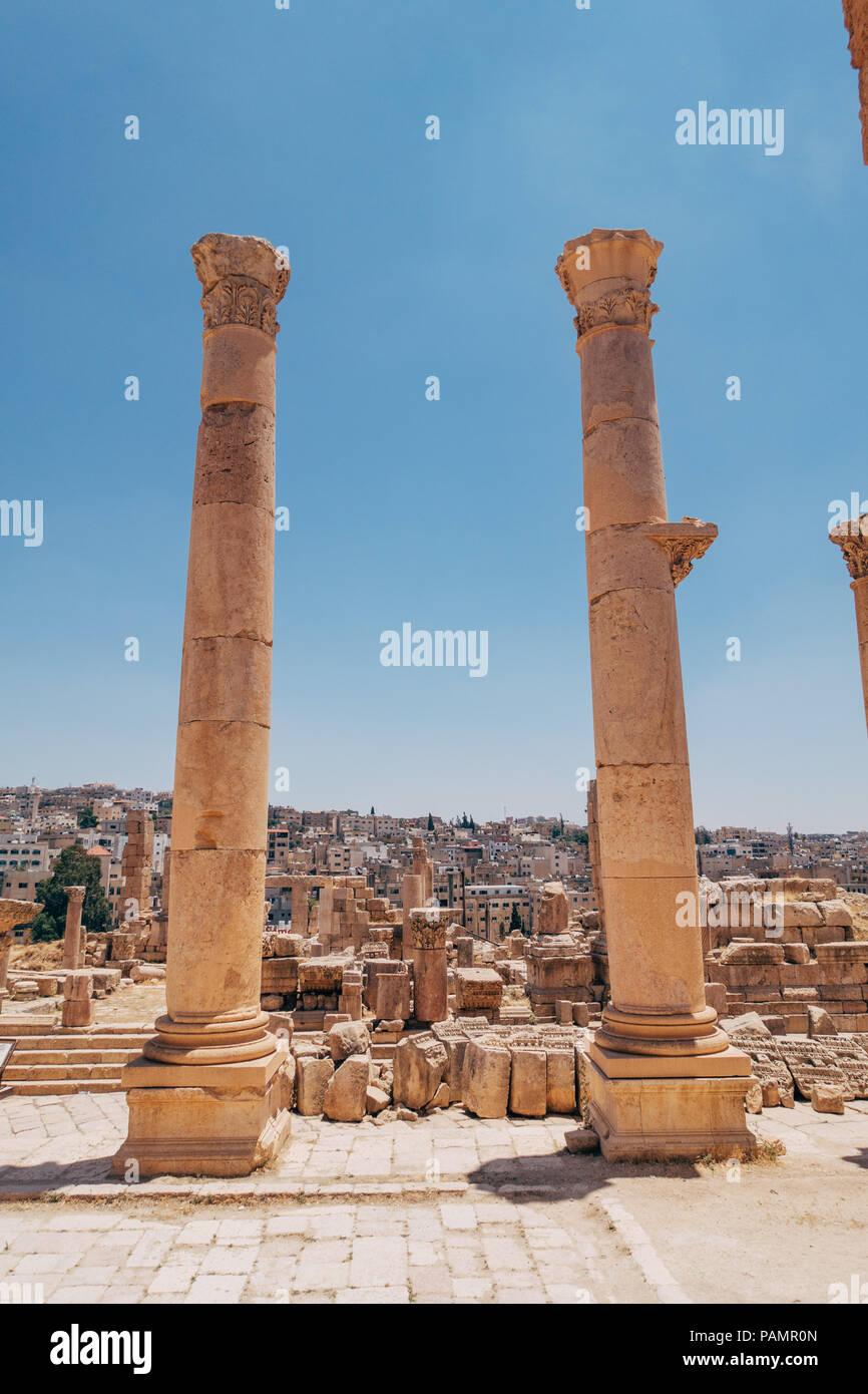 Due antiche colonne greco-romana stand tall all'entrata di un vecchio palazzo di Jerash, Giordania Immagini Stock