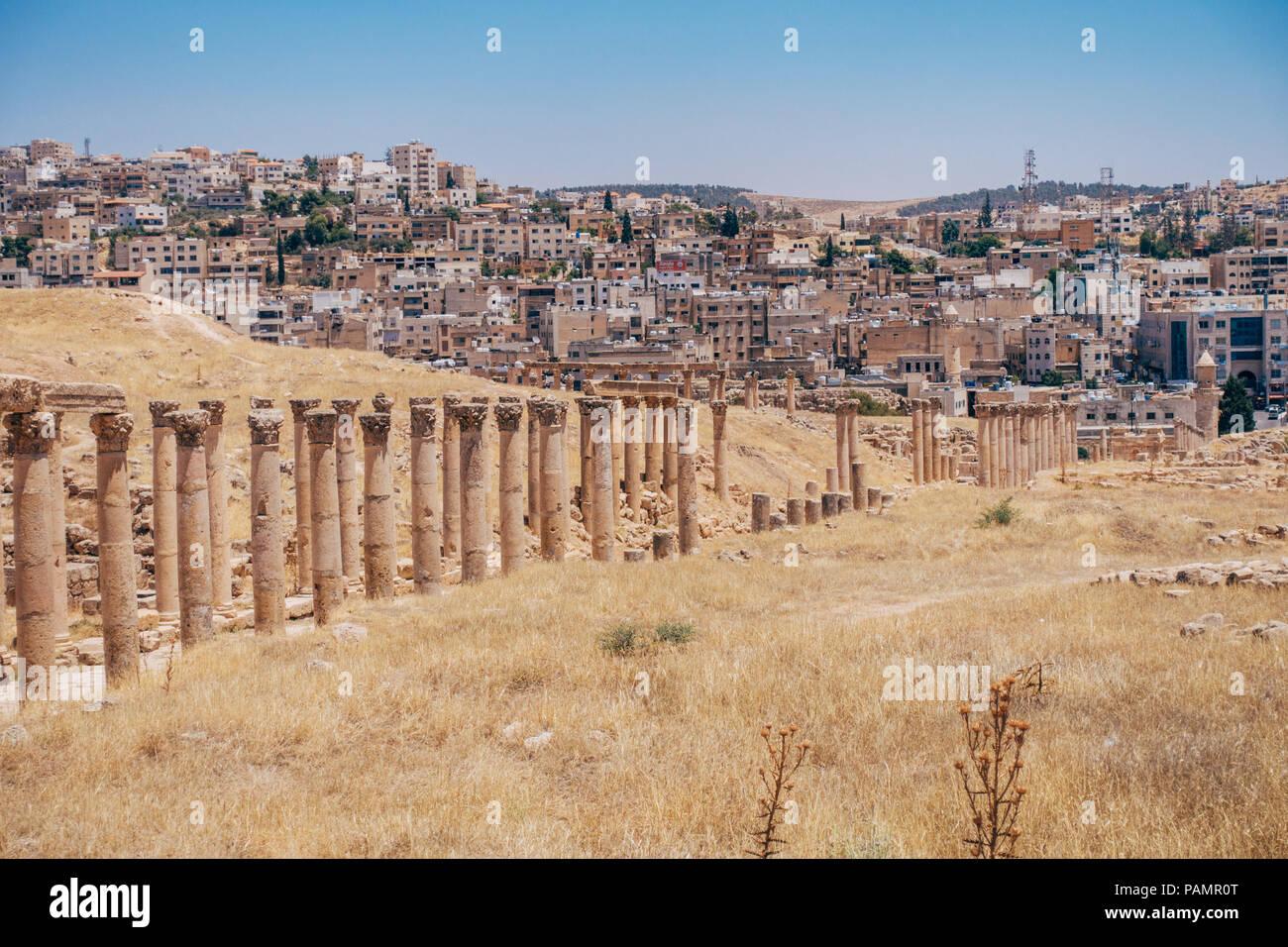 Vecchio antiche colonne greco-romana la linea strade lastricate in una calda giornata d'estate in Jerash, Giordania Immagini Stock