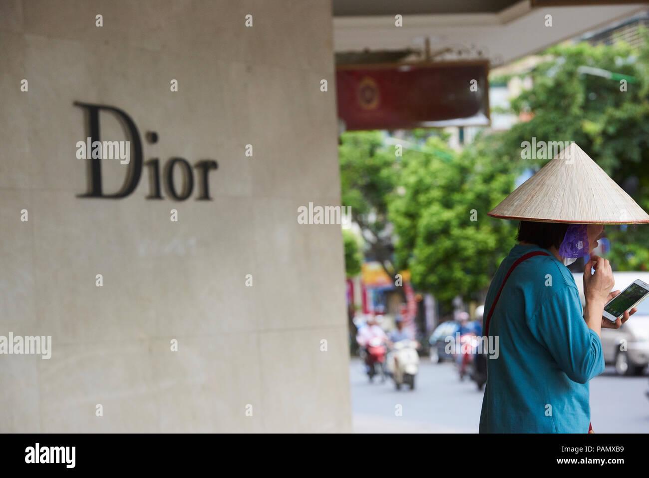 Una donna che indossa un tradizionale vietnamita cappello conico di paglia  sorge al di fuori di fac99693bd1a