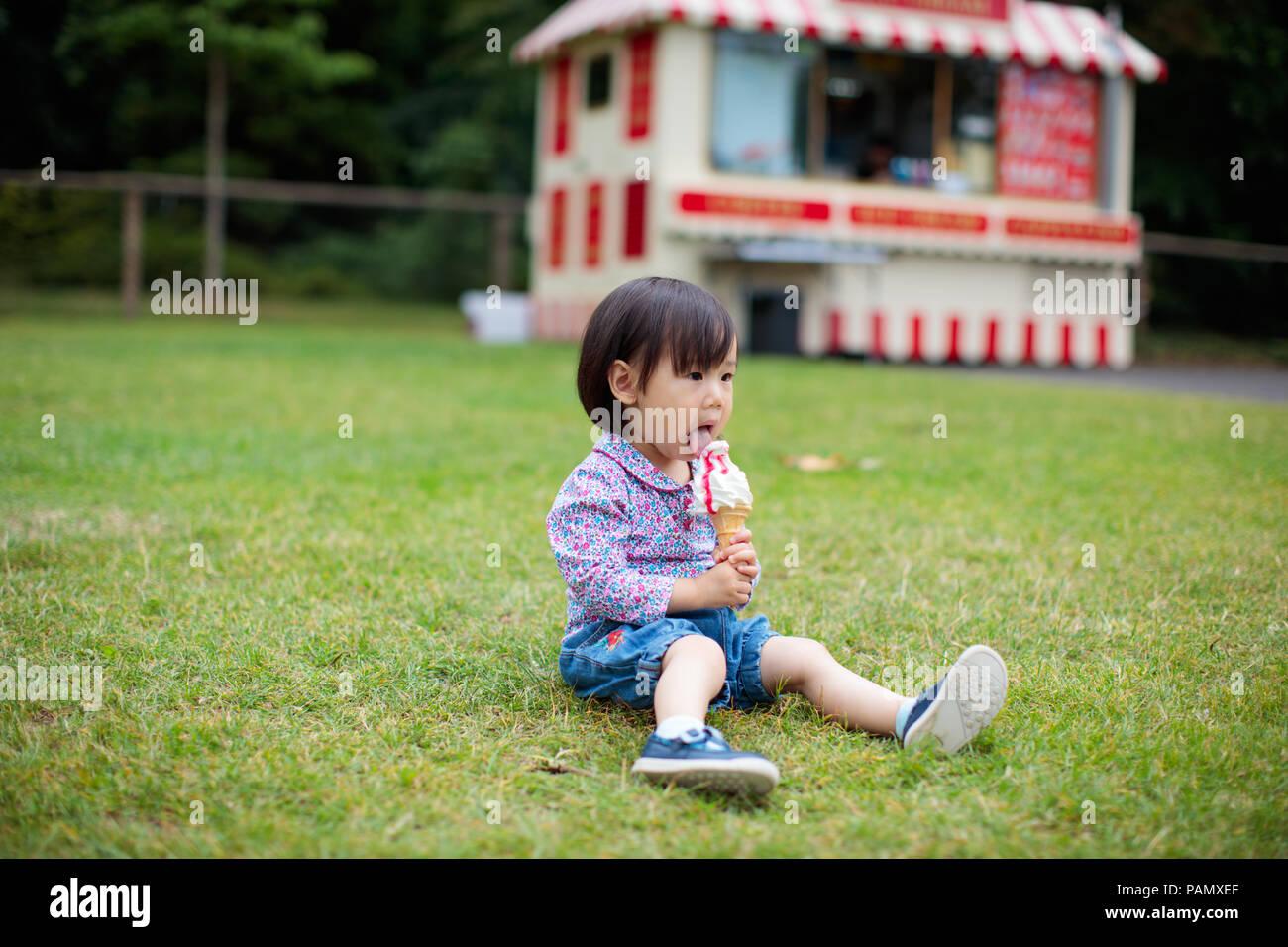 Baby ragazza seduta sul prato estivo e mangiare gelato Immagini Stock