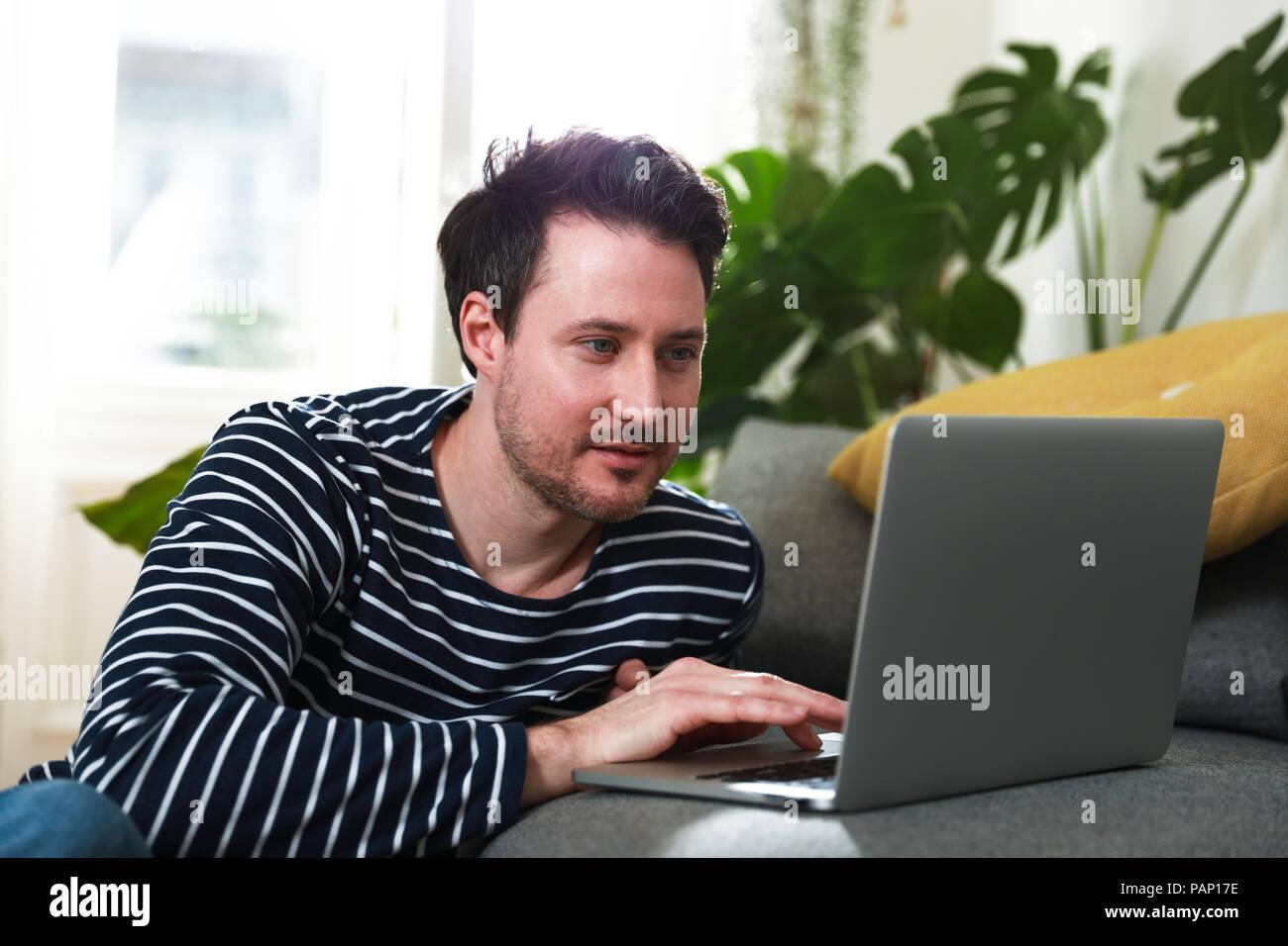 Uomo seduto a casa, utilizzando laptop Immagini Stock