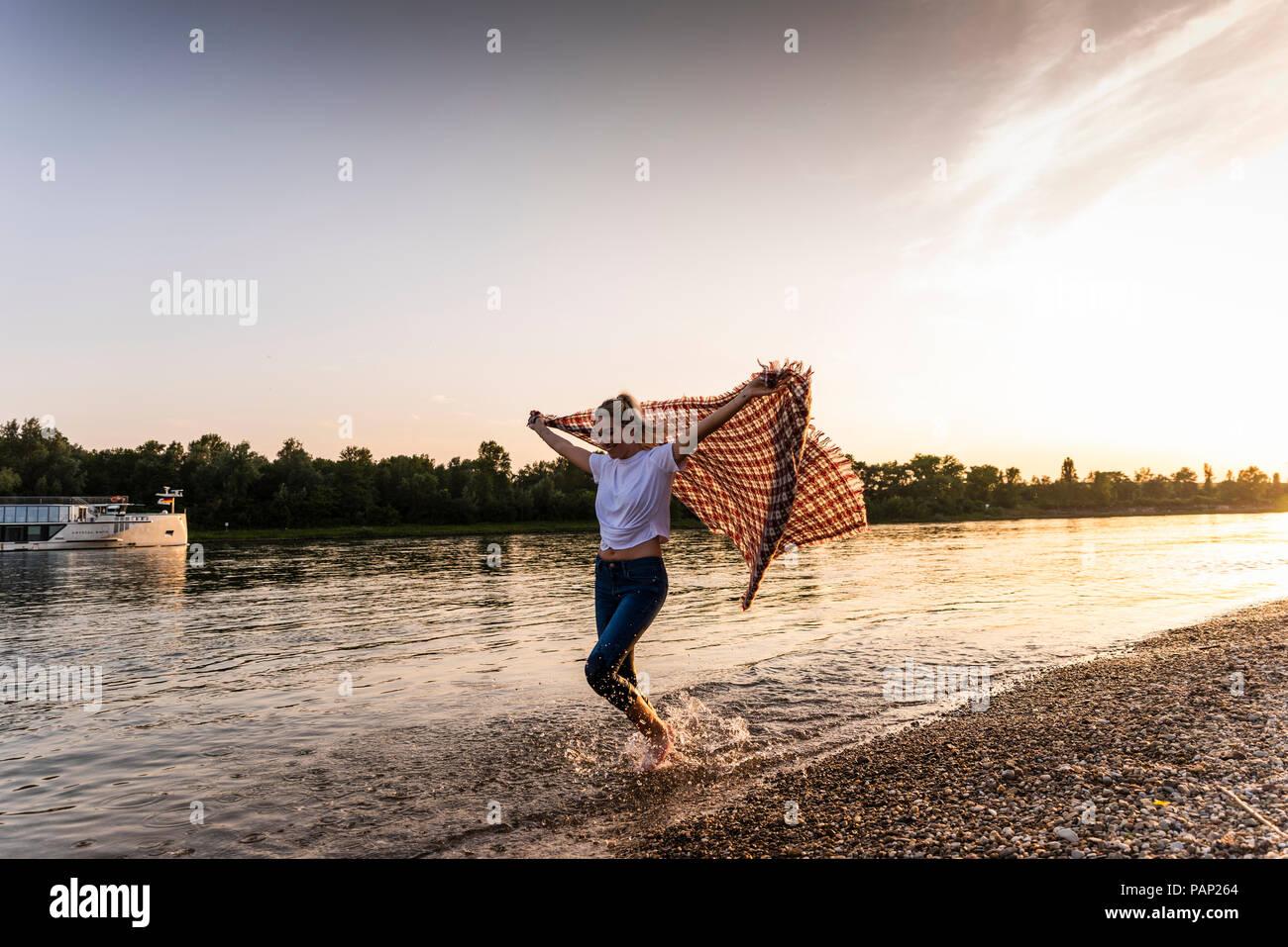 Giovane donna camminare a piedi scalzi su riverside con coperta Immagini Stock