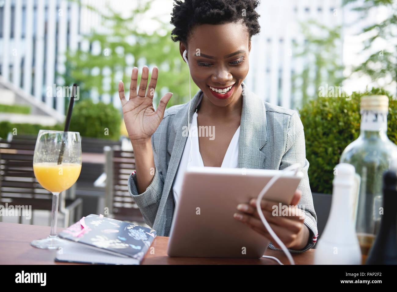 Ritratto di sorridere imprenditrice avente video conferenza con tavoletta digitale al cafè sul marciapiede Immagini Stock