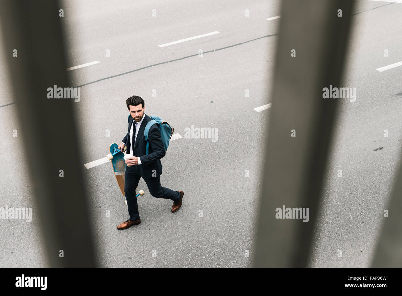 Imprenditore con caffè da asporto e skateboard a camminare sulla strada Foto Stock