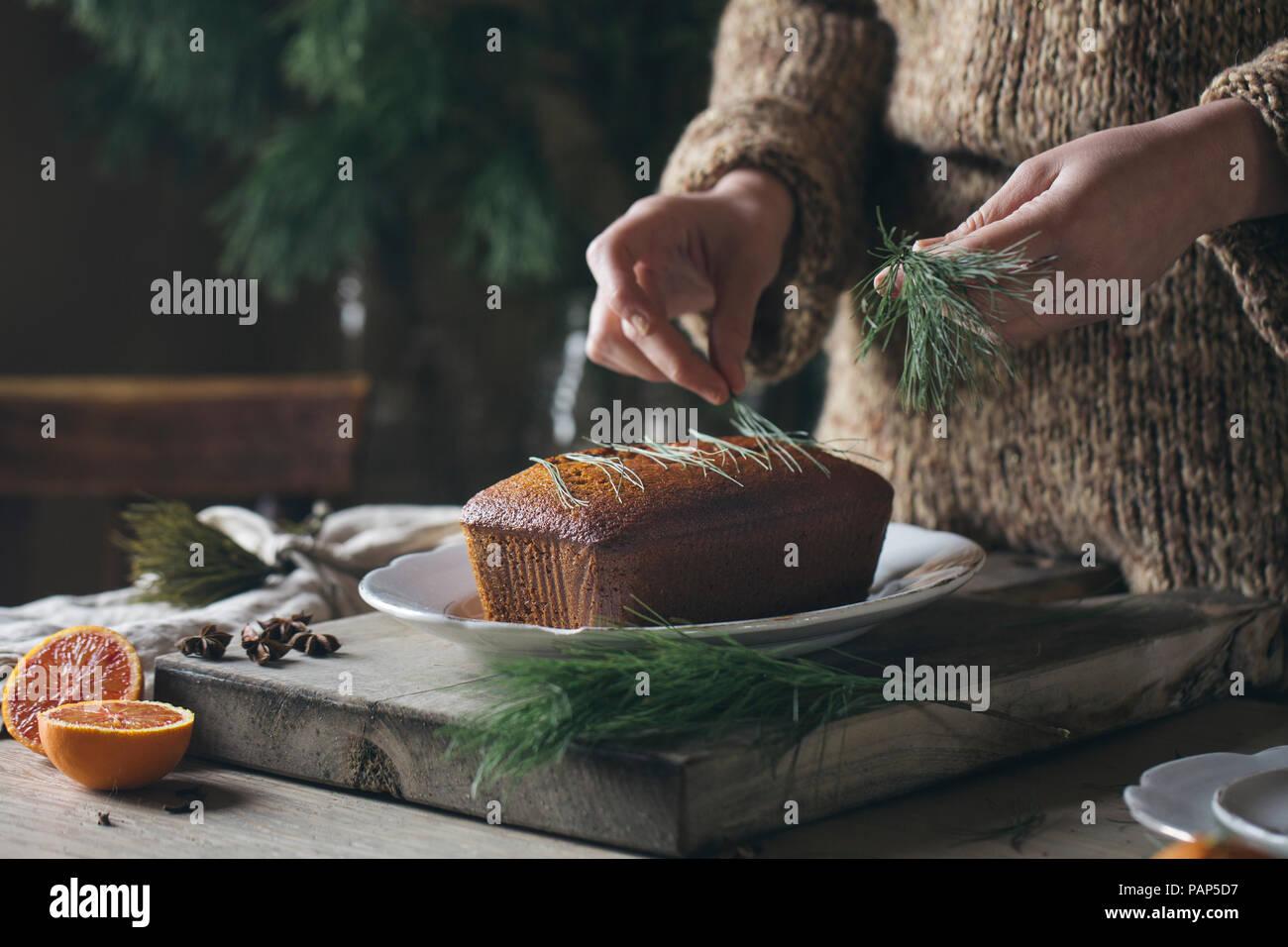 Donna con le mani in mano in casa decorazione torta di Natale Immagini Stock