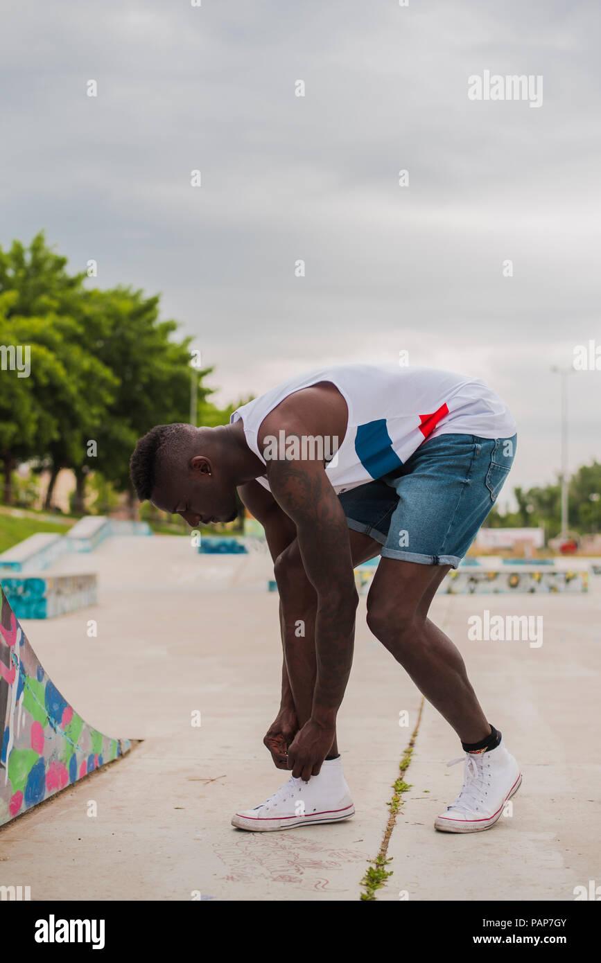 Giovane uomo in skatepark, scarpe di legatura Immagini Stock