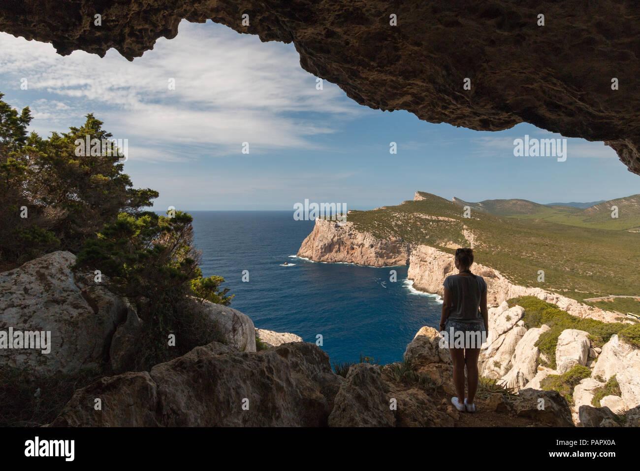 Donna che guarda al paesaggio dalla Grotta dei vasi rotti accanto a Capo Caccia sull'isola italiana di Sardegna Immagini Stock