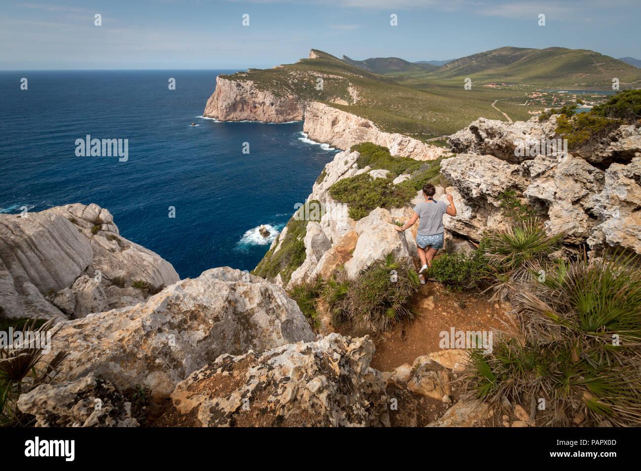 Donna escursioni nel paesaggio visto dalla Grotta dei vasi rotti accanto a Capo Caccia sull'isola italiana di Sardegna Immagini Stock