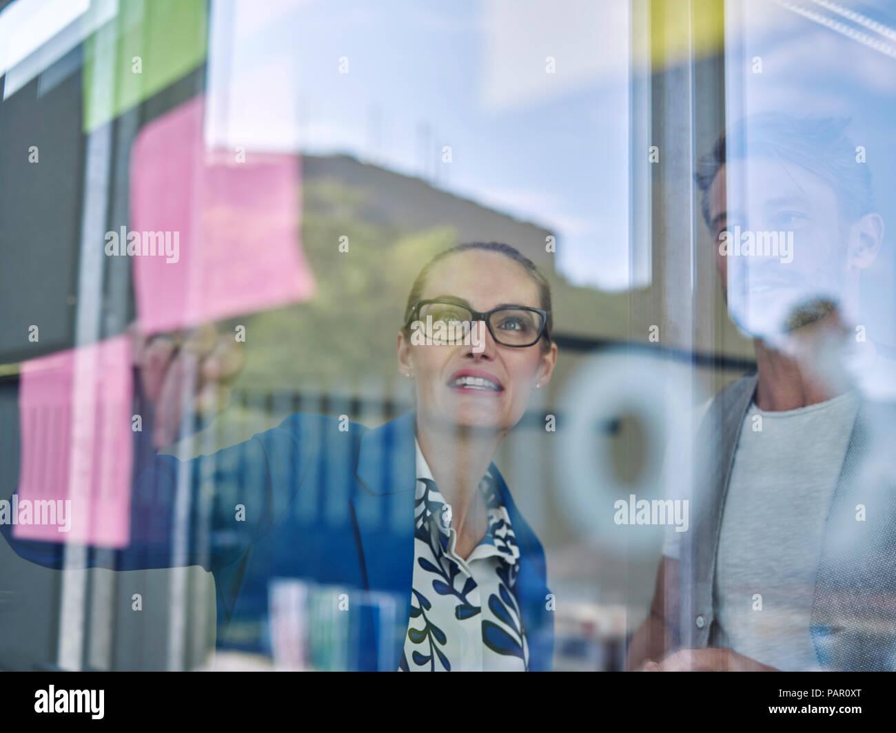 I colleghi guardando il foglietto adesivo al pannello in vetro Immagini Stock